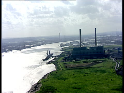 track right past large industrial building with chimneys in distant background thames estuary - thames river stock videos and b-roll footage