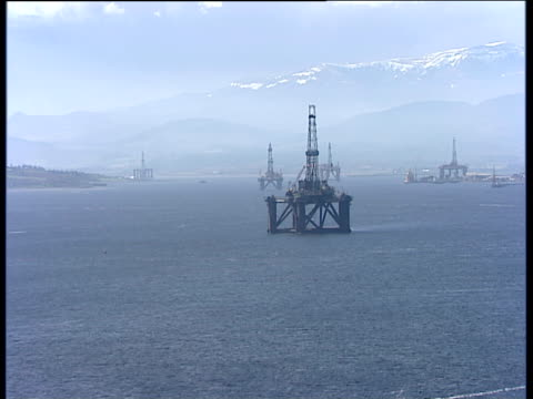track right past series of oil platforms in cromarty firth ross-shire - oil rig stock-videos und b-roll-filmmaterial