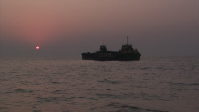 Track right past silhouette of ship orange sun in distance Available in HD.