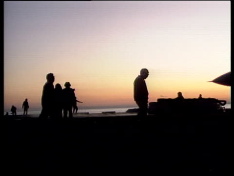 Track right past silhouetted US sailors walking by US F14 plane under orange sky Adriatic Sea 1994