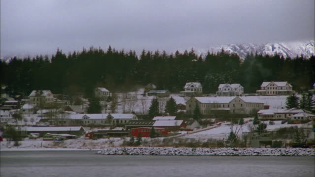 track right past snow covered houses on lakeshore with green trees and mountains in distance, alaska available in hd. - lakeshore stock videos & royalty-free footage