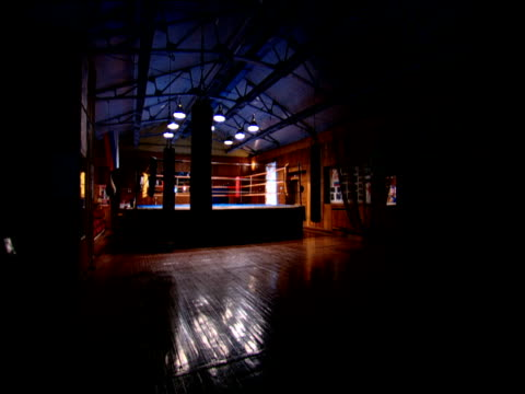 Track right through empty boxing gym with punch bags swinging Russia