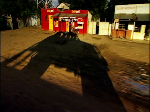track right through nakuru as elongated shadow of 4x4 vehicle is cast on dusty track kenya - lunghezza video stock e b–roll
