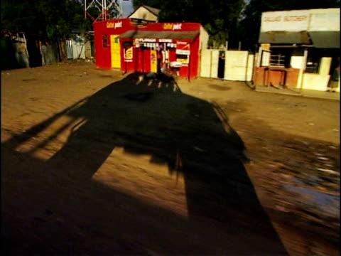 track right through nakuru as elongated shadow of 4x4 vehicle is cast on dusty track kenya - 長さ点の映像素材/bロール