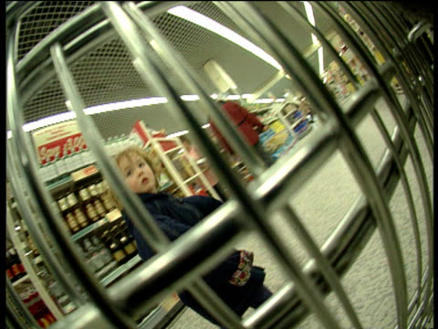 track right through shopping trolley as it is wheeled through shop - 1997 stock videos and b-roll footage