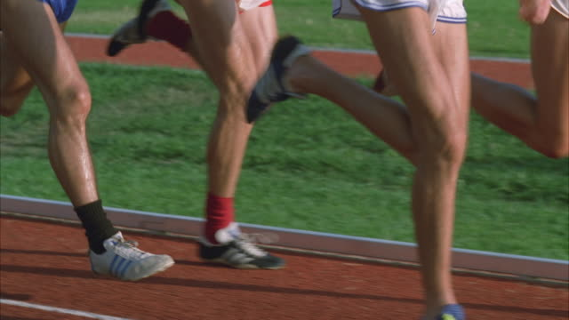 slo mo co zo ms track runners running around track, low section - shorts stock-videos und b-roll-filmmaterial