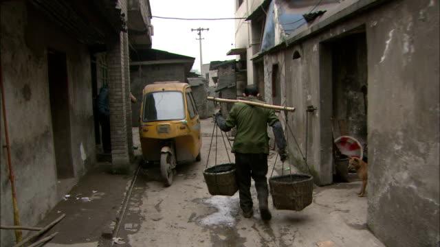 vídeos de stock e filmes b-roll de track shot and tilt down of charcoal man passing through residential lane - pobreza questão social