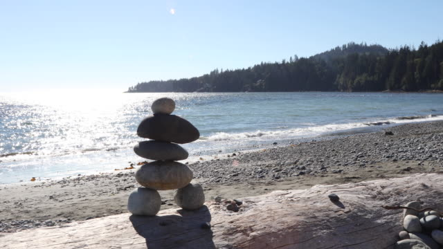 track shot of inukshuk on log, sea and surf behind - western usa stock videos & royalty-free footage