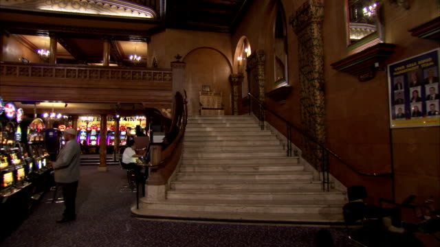 stockvideo's en b-roll-footage met track through the ornate art deco foyer of a former cinema, up polished stone staircase and through doors to auditorium, london available in hd. - bingo