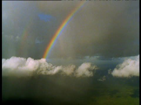 track towards cloud and rainbow over forest, papua new guinea - rainbow stock videos & royalty-free footage