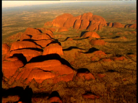 track towards glowing red sandstone olgas rising out of outback, northern territory, australia - sandstone stock videos & royalty-free footage