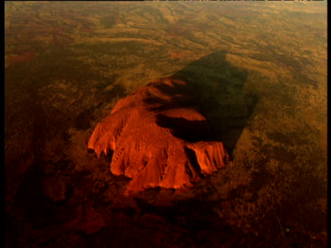 track towards red sandstone uluru rock rising out of outback at sunset, northern territory, australia - エアーズロック点の映像素材/bロール