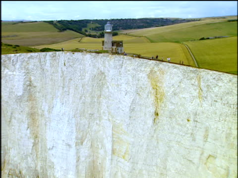 track up and away from cliff face to include the belle tout lighthouse beachy head - kreidefelsen stock-videos und b-roll-filmmaterial