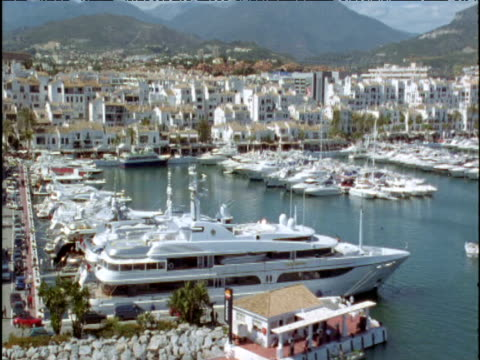 Track up over marina and sea front properties Marbella Spain