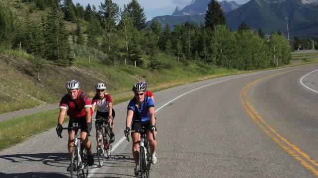 track view of biking peloton of 4 bikers following mtn road - プロトン点の映像素材/bロール