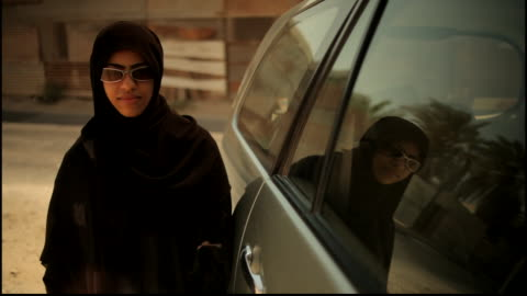 track-in towards a bahraini woman standing by her car and smiling into the camera. - one girl only stock videos & royalty-free footage