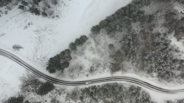 tracking a car from above as it drives down a winding wintery road in heavy snowfall - european alps stock videos & royalty-free footage