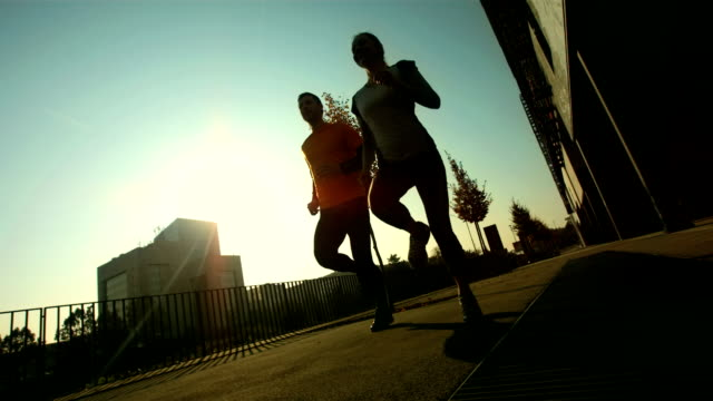 stockvideo's en b-roll-footage met hd: tracking a couple jogging on sidewalk - rennen