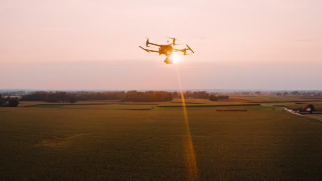 空中日没時にフィールドの上を飛ぶドローンを追跡 - ファームハウス点の映像素材/bロール