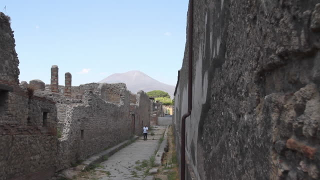 Tracking a lone figure on an ancient street in Pompeii, the volcano that destroyed the city, Mount Vesuvius, towering behind, Napoli