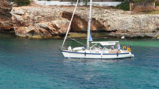 tracking a sailboat as it moves through the water along a rocky coastline, with blue rippled water and bright sunlight - mallorca, spain - majorca stock videos & royalty-free footage