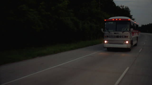 tracking a silver tour bus on a highway. - tour bus stock videos and b-roll footage