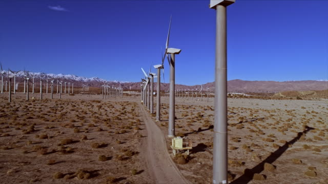 ws tracking along wind turbines in wind farm near snowcapped san gorgonio mountain pass in the san bernadino mountains and interstate 10 - palm springs california stock videos & royalty-free footage