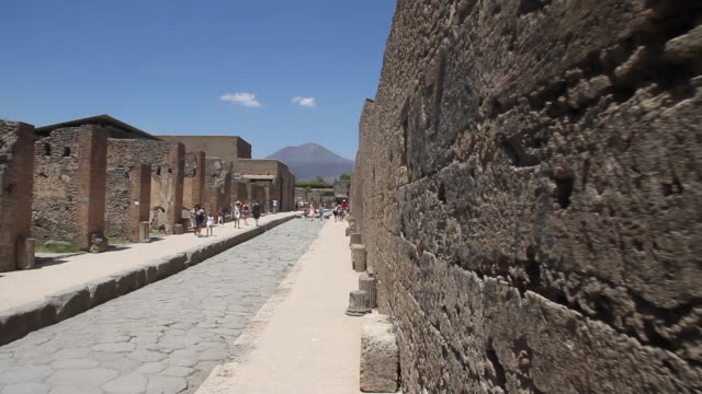 tracking an ancient road in pompeii, the volcano that destroyed the city, mount vesuvius, towering behind, napoli - pietra materiale da costruzione video stock e b–roll