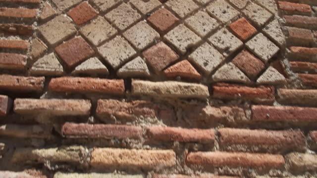 Tracking ancient brickwork in Pompeii ruin to reveal decorative stone phallus or penis, Napoli