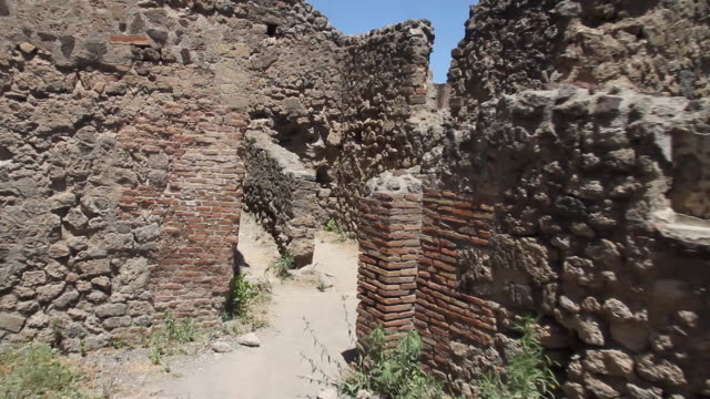 Tracking back through the ruins of ancient roman houses to reveal a kitchen counter in a Thermopolium or 'cook shop' in Pompeii, Napoli