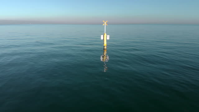 vídeos de stock e filmes b-roll de tracking back to reveal a channel marker with a yellow cross and warnings, brighton, australia - water's edge