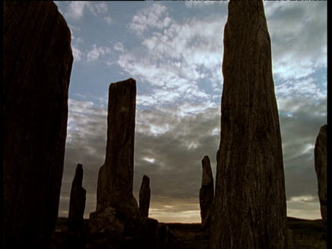 Tracking backwards away from Callanish stones in silhouette beneath grey clouds, Outer Hebrides