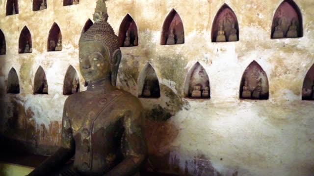 vidéos et rushes de suivi en arrière à travers des milliers de statues de bouddha au wat si saket, vientiane, laos - assis en tailleur