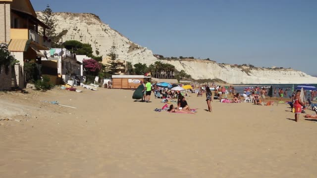 vidéos et rushes de tracking beach and bathers at a small beach next to the stair of the turks, sicily - strate géologique