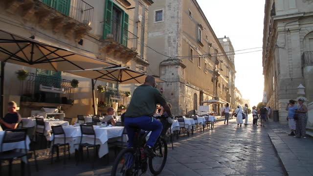 Tracking behind a cyclist passing diners and restaurant tables lining the Piazza Municipal, Noto, Sicily, Italy