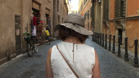 tracking behind a female tourist walking down a cobble stoned, classic roman street, rome - cobblestone stock videos & royalty-free footage