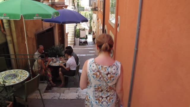 vidéos et rushes de tracking behind a woman walking past a cafe in the very narrow and steep streets in the picturesque town of taormina in sicily - tourisme