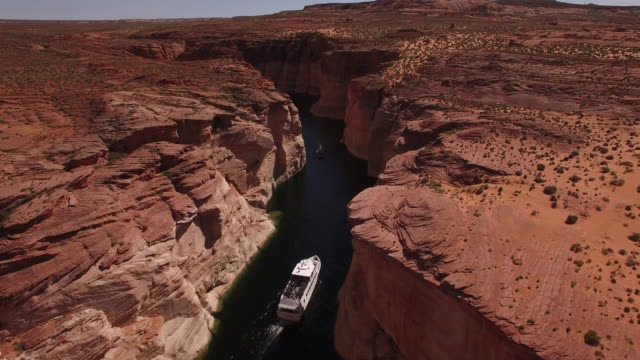 tracking behind boat on lake powell 4k, drone aerial view of kayak and boat on lake powell reservoir and colorado river, with beautiful sand stone formations and water grand canyon located in glen canyon, arizona - lake powell stock videos and b-roll footage