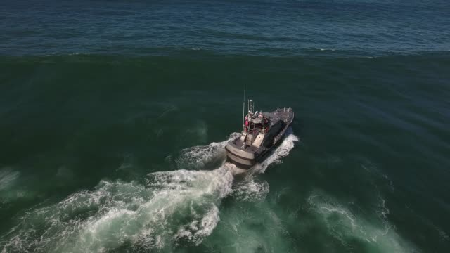 tracking behind boat over waves coast guard, rough seas, rouge wave crashing over boat water, Drone aerial video, 4k, rescue, marine, pacific, tide, surge, danger, dangerous waves raw.mov