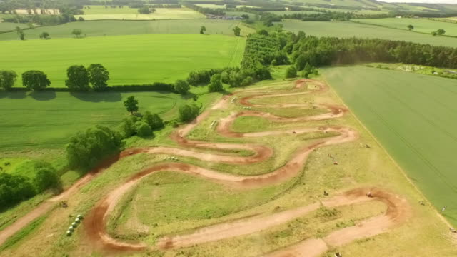 Tracking birds eye view drone shot of quad bikes / off road vehicle on a dusty dirt track
