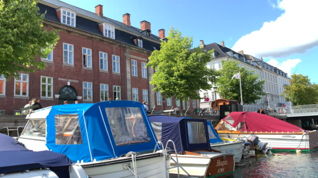 tracking classic copenhagen apartment buildings overlooking a canal in copenhagen - regione dell'oresund video stock e b–roll