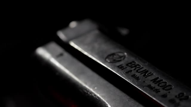 Tracking close up of a Beretta Bruni revolver against black, shallow depth of field
