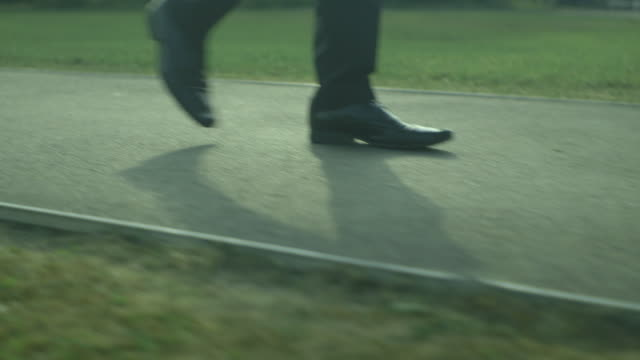 tracking close-up shot of the legs of a smartly-shod man walking along a tarmacked path in a grassy area, uk. - surface level stock videos & royalty-free footage