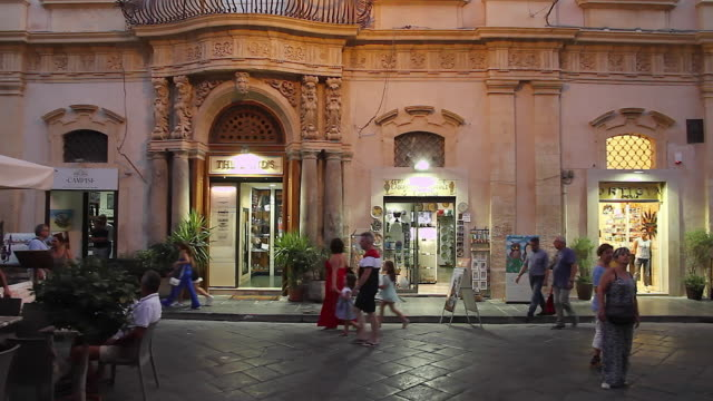 Tracking diners and restaurant tables lining the Piazza Municipal, Noto, Sicily, Italy