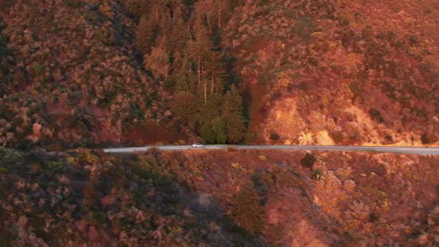 ビッグ ・ サーでパシフィック コースト ハイウェイに車の追跡ドローン ショット - トラッキングショット点の映像素材/bロール