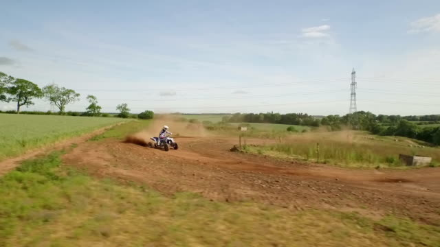 tracking drone shot of quad bikes / off road vehicle on a dusty dirt track - quadbike stock videos and b-roll footage