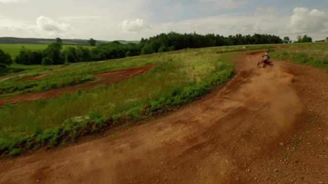 tracking drone shot of quad bikes / off road vehicle on a dusty dirt track - quadbike stock videos & royalty-free footage
