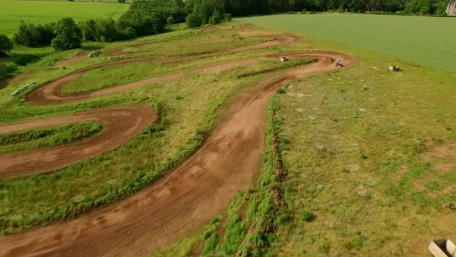 Tracking drone shot of quad bikes / off road vehicle on a dusty dirt track