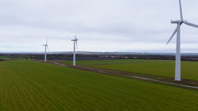 tracking drone shot revealing wind turbines spinning - power station stock videos & royalty-free footage