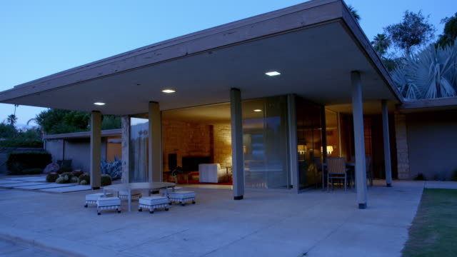 WS tracking exterior patio area of mid-century modern home at dusk featuring large roof overhang supported by square columns, looking into living room and its 1950s original furnishings at night